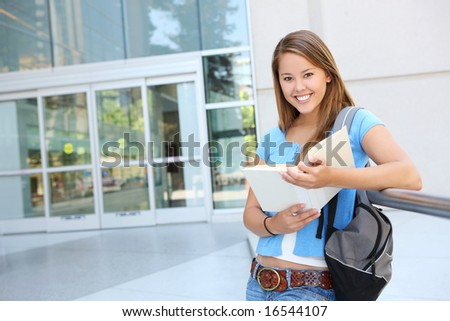 Attractive young woman at school library holding book - stock photo