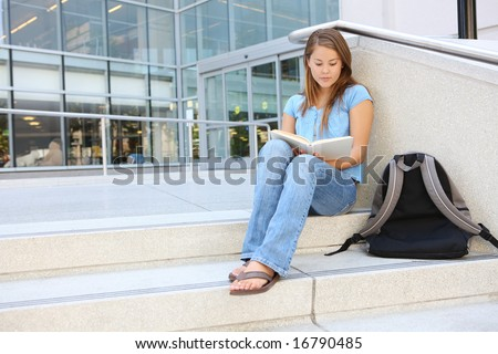 Attractive young woman at school library holding book reading - stock photo