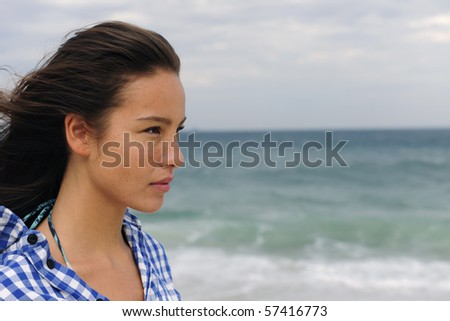 attractive young woman at the sea facing the future - stock photo