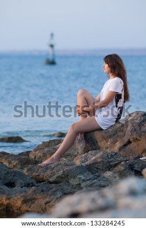 Attractive young woman at the sea. Girl in white t-shirt sits on rocky seashore in evening time