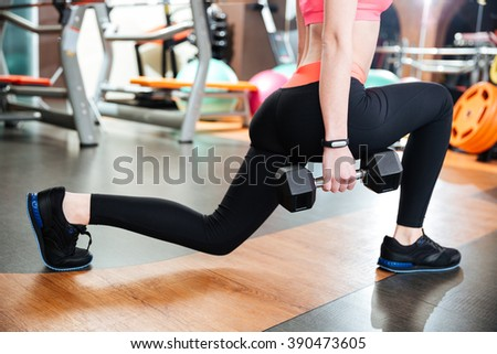 Attractive young woman athlete doing squats with dumbbells in gym - stock photo