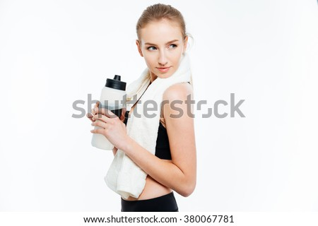 Attractive young woman athlete holding bottle of water and white towel over white background - stock photo