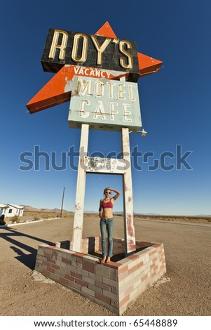 Attractive, young woman being silly at an abandoned roadside motel sign. - stock photo