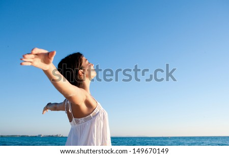 Attractive young woman breathing fresh air while standing on a beach shore with her arms outstretched back, enjoying the intense blue sea and sky at sunset during a vacation. - stock photo
