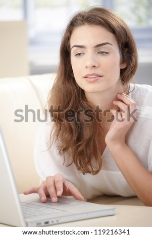 Attractive young woman browsing internet at home, laying on sofa. - stock photo