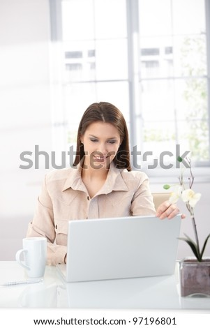 Attractive young woman browsing internet at home, using laptop, smiling.?