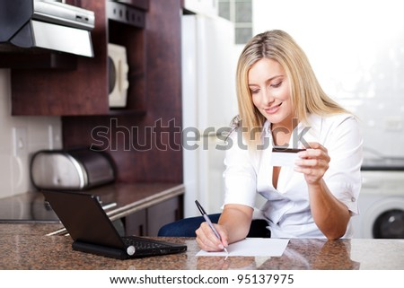 attractive young woman calculating credit card bill
