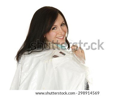 Attractive young woman carrying dry cleaning over shoulder. - stock photo