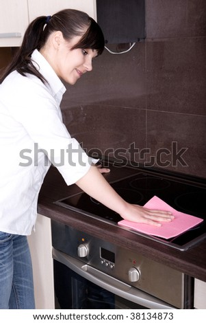 attractive young woman cleaning kitchen - stock photo