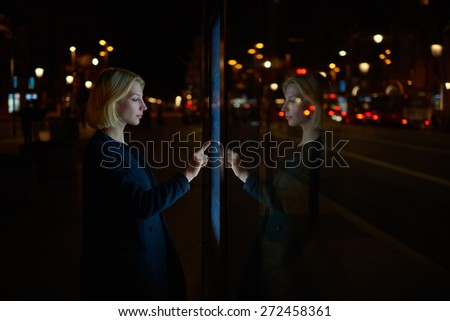 Attractive young woman consults on modern big timetable outdoors, female caucasian tourist touching information kiosk digital screen while standing at night city with beautiful lights on background - stock photo