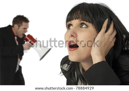Attractive young woman covering ears while angry man yells in electric bullhorn over white.