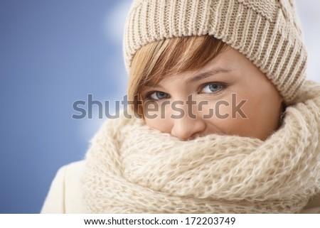 Attractive young woman covering her face with shawl on a cold winter day - stock photo