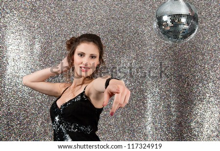 Attractive young woman dancing in a night club with a mirror ball and a silver background.