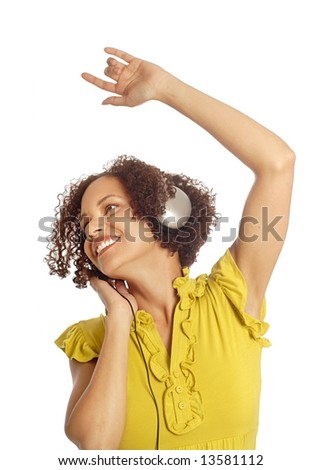 Attractive young woman dancing to music on her headphones - stock photo