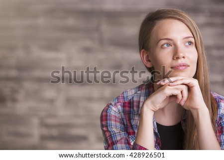 Attractive young woman daydreaming on blurry brown background - stock photo