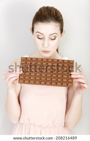Attractive young woman deciding on whether to eat a piece of chocolate. - stock photo