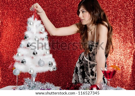 Attractive young woman decorating a small christmas tree while standing in front of a red glitter background.