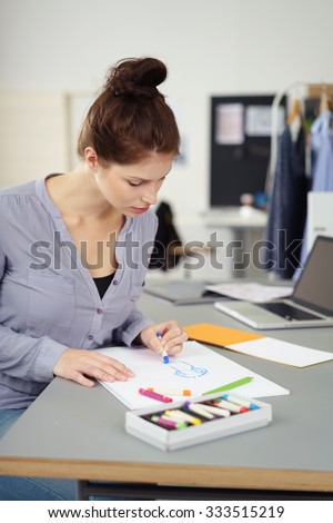 Attractive young woman designing original fashion garments in a her studio sitting at a table sketching an outfit with colorful wax crayons