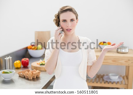 Attractive young woman discussing on the phone standing in the kitchen looking at camera - stock photo