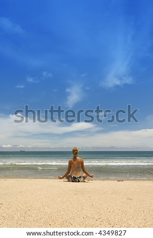 attractive young woman doing Yoga at the beach - stock photo