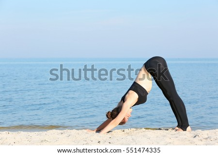 Attractive young woman doing yoga by the sea