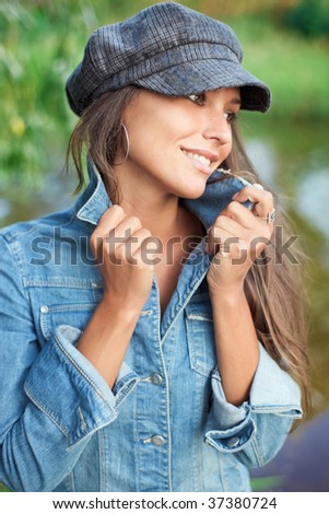 Attractive young woman dressed in jean and beret holding on herself jacket collar - stock photo