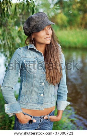 Attractive young woman dressed in jean and beret on the river coast - stock photo