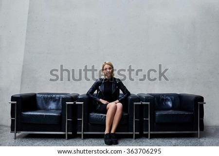 Attractive young woman dressed in trendy clothes during free time sitting alone on a black leather couch in office interior, charming stylish female waiting for someone in hallway of modern studio - stock photo