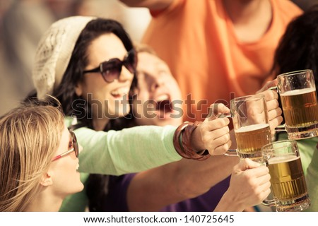 Attractive young woman drinking a beer on a beautiful sunny day - stock photo