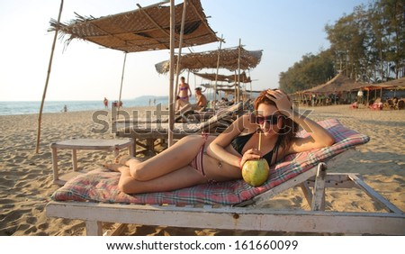 Attractive young woman drinking coconut milk with straw while relaxing on beach - stock photo