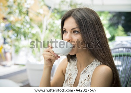 Attractive young woman drinking coffee. - stock photo