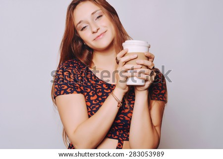 Attractive young woman drinking coffee out of a disposable cup.