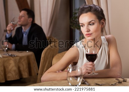 Attractive young woman drinking red wine alone - stock photo