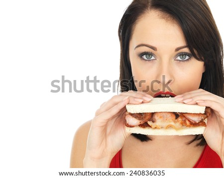 Attractive Young Woman Eating a Bacon Sandwich - stock photo