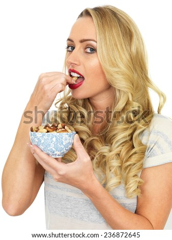 Attractive Young Woman Eating a Bowl of Nuts - stock photo
