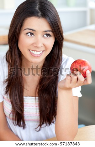 Attractive young woman eating an apple in kitchen - stock photo