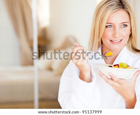 attractive young woman eating fruit salad at home