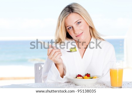 attractive young woman eating healthy breakfast, background is sea view