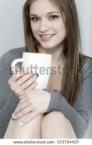 Attractive young woman enjoying a coffee break at home
