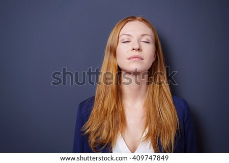 Attractive young woman enjoying a quiet moment standing meditating with her eyes closed and head tilted back, dark studio background with copy space - stock photo