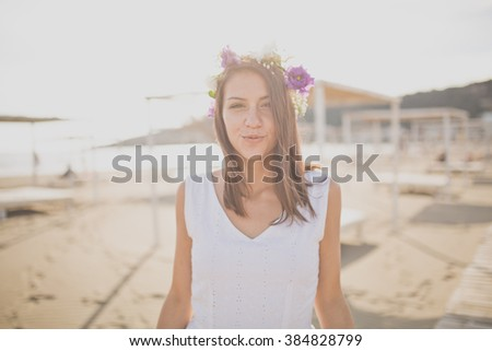 Attractive young woman enjoying her time on the sandy beach.Wearing flower headpiece.Hopeless romantic in dress and flowers in hair.Spring/summer lifestyle vacation mood.Vintage effect,soft focus - stock photo