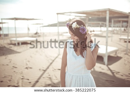 Attractive young woman enjoying on the sandy beach.Wearing flower headpiece.Hopeless romantic woman in white dress and flowers in her hair.Spring/ summer lifestyle vacation mood - stock photo