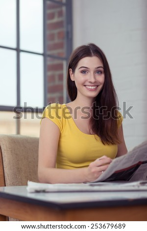 Attractive young woman enjoying reading the morning the newspaper looking at the camera with a beaming smile - stock photo