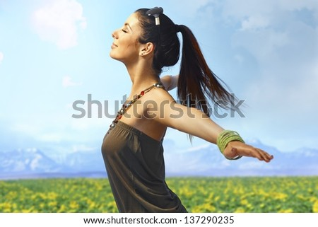 Attractive young woman enjoying summer sun and wind on the meadow. Side view, pretending to fly. - stock photo