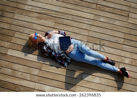 Attractive young woman enjoying sunshine while lying on the wooden pier with her tablet computer, female carefree freelancer girl resting after work outside, young female enjoy her holiday or break - stock photo
