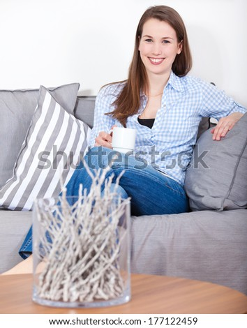 Attractive young woman enjoys a cup of coffee - stock photo
