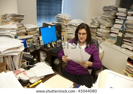 Attractive young woman executive at work in a very messy office - stock photo