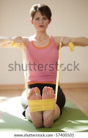 Attractive young woman exercises with resistance bands around her feet. Vertical shot. - stock photo