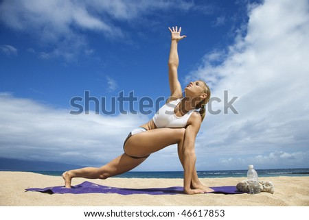 Attractive young woman extends an arm while and doing yoga on beach with the ocean in the background. Horizontal shot. - stock photo