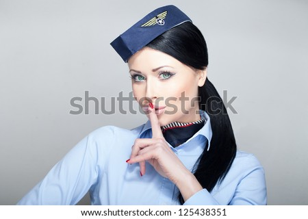 Attractive young woman flight attendant stewardess with green eyes quieting down - stock photo